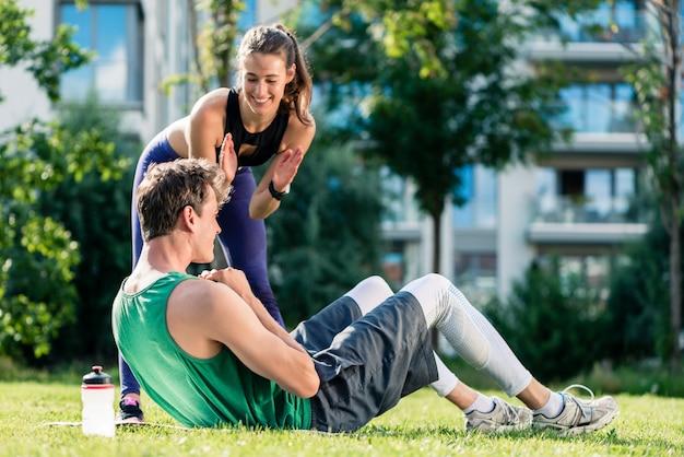 Mulher, ajudando o homem a fazer exercício