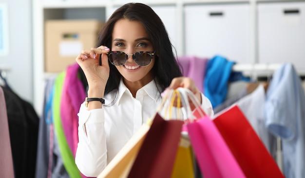 Mulher ajusta óculos de sol mostrando pacotes
