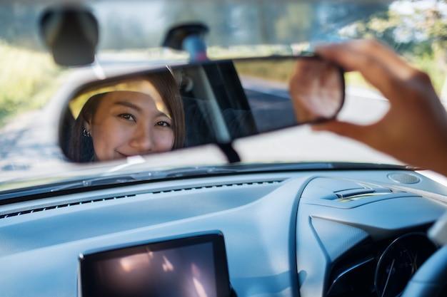 Mulher ajustando um espelho retrovisor enquanto dirige