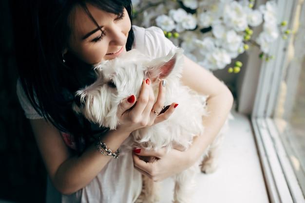 Mulher alegre abraçando com cachorro Foto gratuita