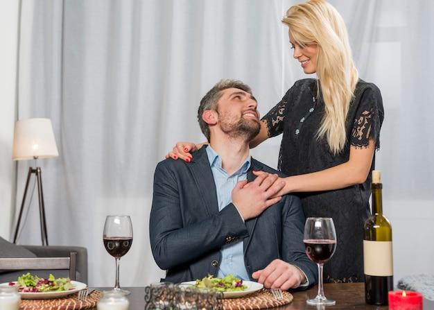 Mulher alegre, abraçando o homem na mesa com pratos e copos