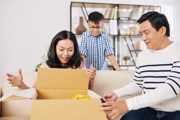 Mulher alegre abrindo uma caixa grande que recebeu de seu marido e filho de aniversário