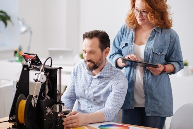 Mulher alegre, agradável e encantada, parada atrás de seu colega, segurando um tablet enquanto olha para a impressora 3d