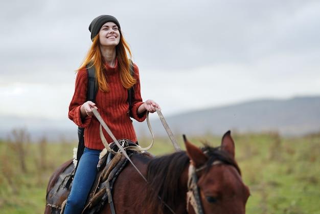 Mulher alegre alpinista andando a cavalo na montanha.
