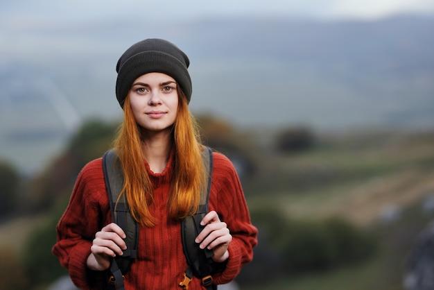 Mulher alegre alpinista com mochila nas montanhas, estilo de vida de aventura ao ar livre