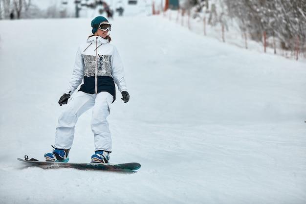 Mulher alegre andando de snowboard nas montanhas no inverno