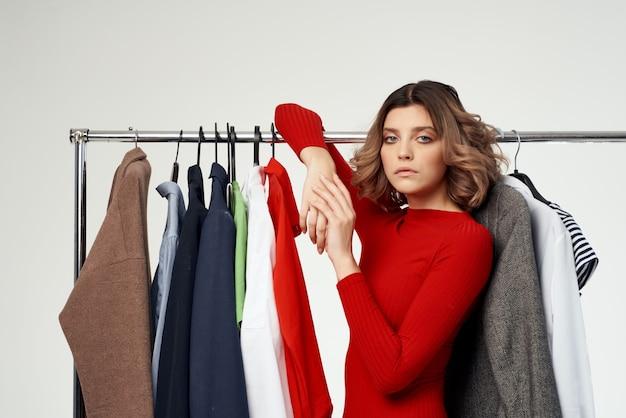Mulher alegre ao lado de roupas de moda diversão varejo luz de fundo. foto de alta qualidade