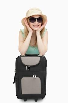 Mulher alegre, apoiando-se em uma mala enquanto está sentado