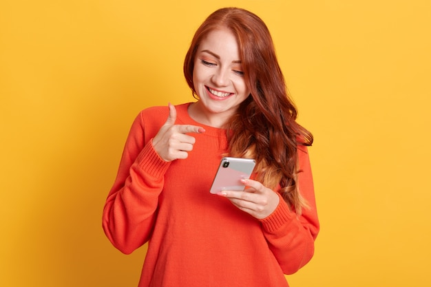 Mulher alegre apontando para a tela do seu smartphone com o dedo indicador, olhando para o celular com um sorriso encantador