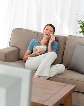 Mulher alegre assistindo televisão e comendo pipoca