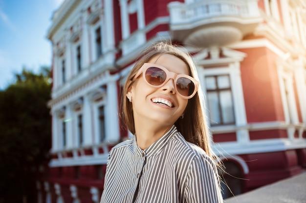 Mulher alegre bonita jovem em óculos de sol andando pela cidade, sorrindo.