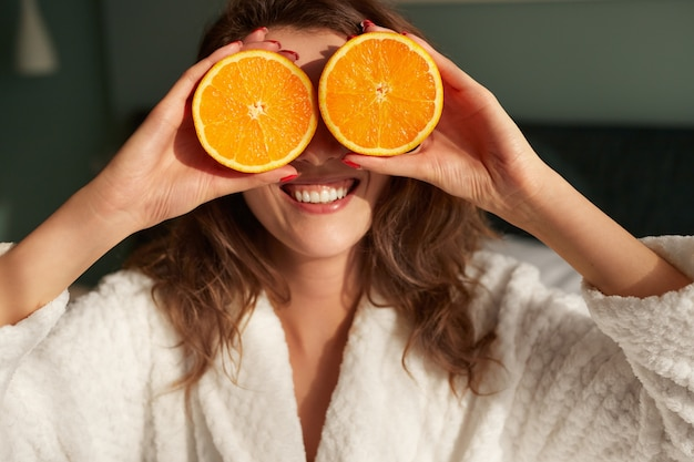 Mulher alegre cobrindo os olhos com metades laranja