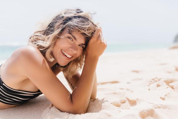 Mulher alegre com a pele bronzeada deitada na areia. rindo atraente garota de biquíni, relaxando na praia.