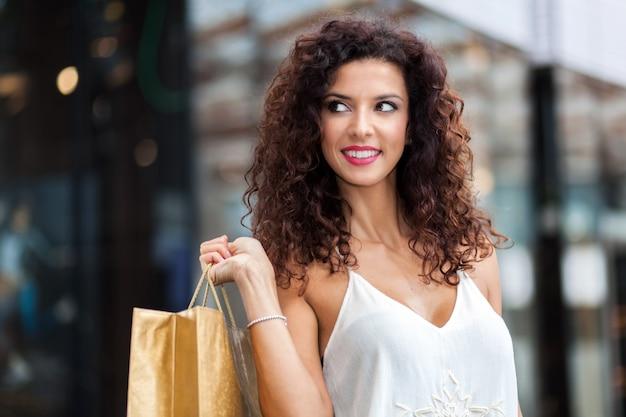 Mulher alegre com a sacola de compras na cidade