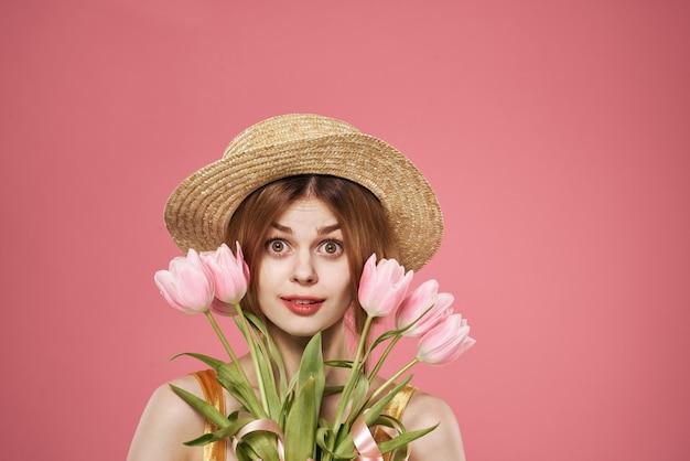 Mulher alegre com buquê de flores cortadas vista de fundo rosa. foto de alta qualidade