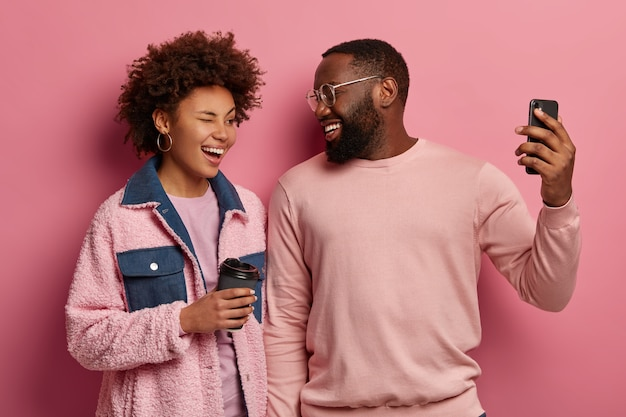 Mulher alegre com cabelo afro piscando os olhos, homem barbudo positivo segurando um telefone celular