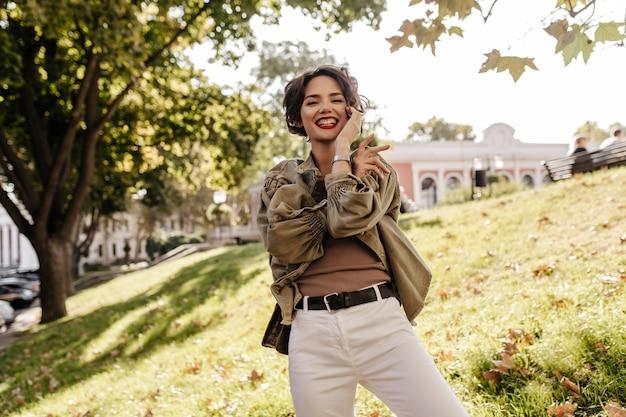 Mulher alegre com cabelo curto e encaracolado em calças brancas com cinto sorrindo lá fora. senhora na moda em jaqueta jeans verde-oliva rindo ao ar livre.