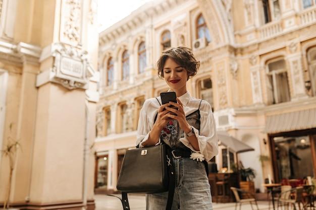 Mulher alegre com cabelo curto, segurando o telefone na rua. mulher elegante em camisa e calça jeans com bolsa preta, sorrindo na cidade.