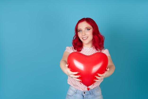 Mulher alegre com cabelo ruivo segura para a câmera um balão voador vermelho em forma de coração