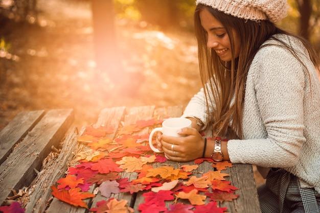 Mulher alegre com caneca na mesa na parte de outono