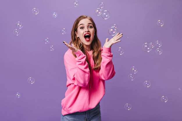 Mulher alegre com capuz rosa surpresa olhando para a câmera e brincando com bolhas