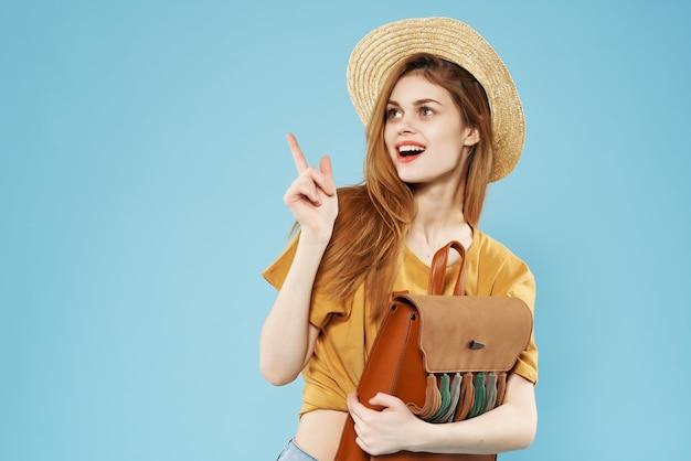 Mulher alegre com chapéu e mochila nas mãos posando fashion lifestyle