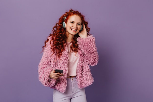 Mulher alegre com fechaduras vermelhas vestida de eco-casaco rosa ri enquanto ouve uma música em fones de ouvido no espaço lilás.