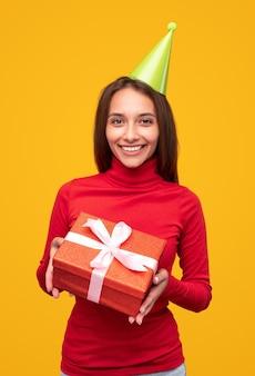 Mulher alegre com gola alta vermelha e chapéu de festa verde sorrindo para a câmera e demonstrando o presente durante a festa de aniversário contra um fundo amarelo