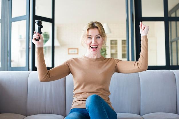 Mulher alegre com joystick no sofá
