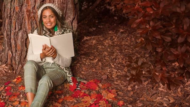 Mulher alegre com livro sentado na floresta