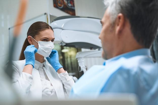 Mulher alegre com máscara e luvas estéreis tratando homem na cadeira durante sua visita à clínica odontológica