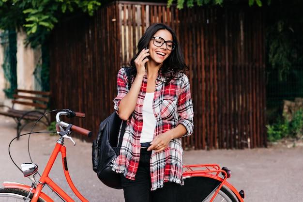 Mulher alegre com mochila de couro preto, falando no telefone na rua. graciosa garota de cabelos negros ao lado da bicicleta vermelha.