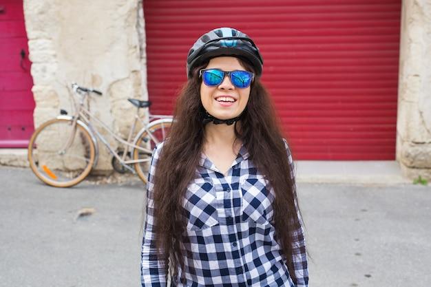 Mulher alegre com óculos escuros e capacete na porta vermelha de fundo e bicicleta