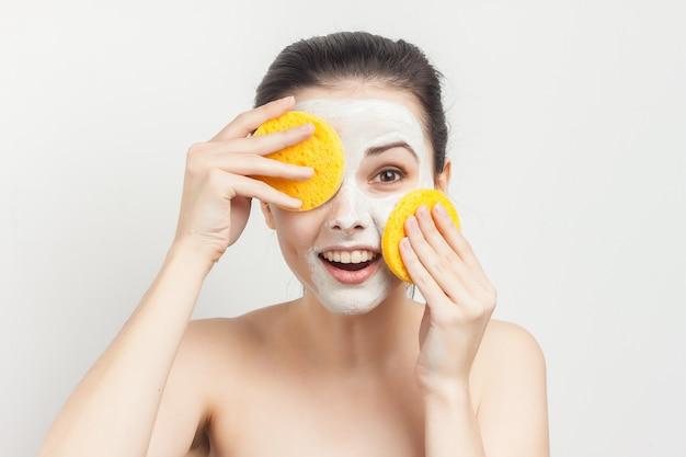 Mulher alegre com ombros nus e escova nas mãos.