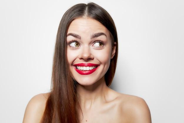 Mulher alegre com ombros nus e sorriso; lábios vermelhos parecem divertidos de lado