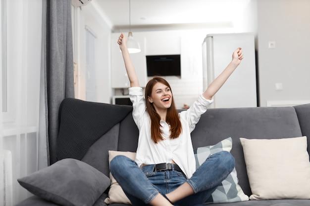 Mulher alegre com os braços levantados sentada no sofá se divertindo e relaxando em casa