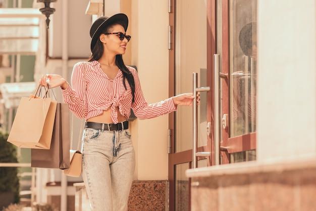 Mulher alegre com sacos de papel colocando a mão na maçaneta da porta