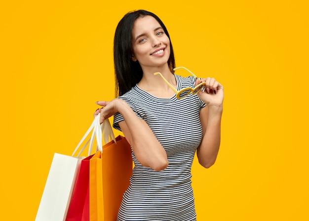 Mulher alegre com sacos de papel e óculos de sol