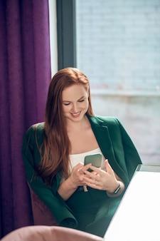 Mulher alegre com smartphone à espera de uma reunião no café