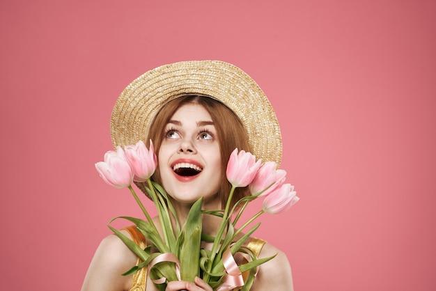 Mulher alegre com um buquê de flores recortadas com vista para o fundo rosa