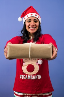 Mulher alegre com um chapéu de papai noel dando um presente de natal