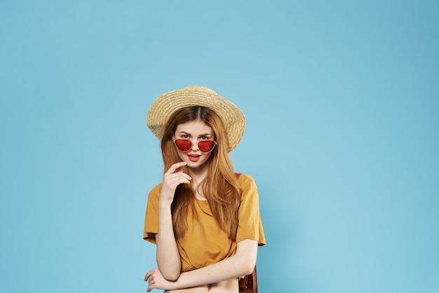 Mulher alegre com um chapéu e óculos de sol na mochila com fundo azul