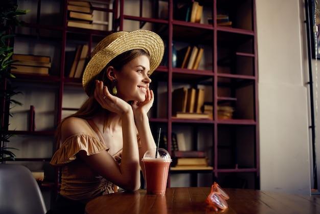 Mulher alegre com um livro nas mãos de uma cafeteria