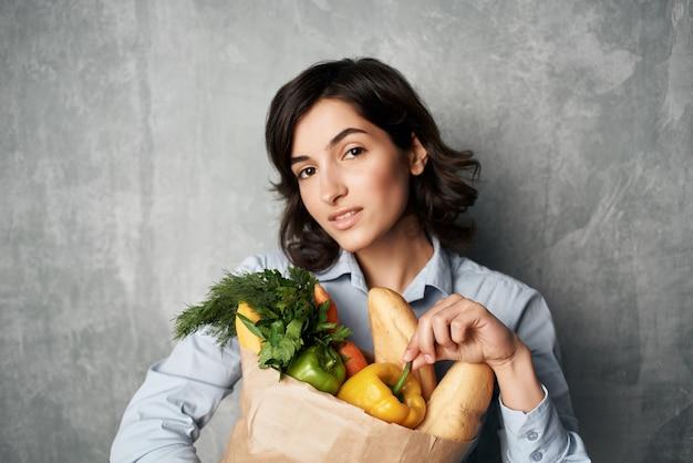 Mulher alegre com um pacote de mantimentos, comprando legumes no supermercado