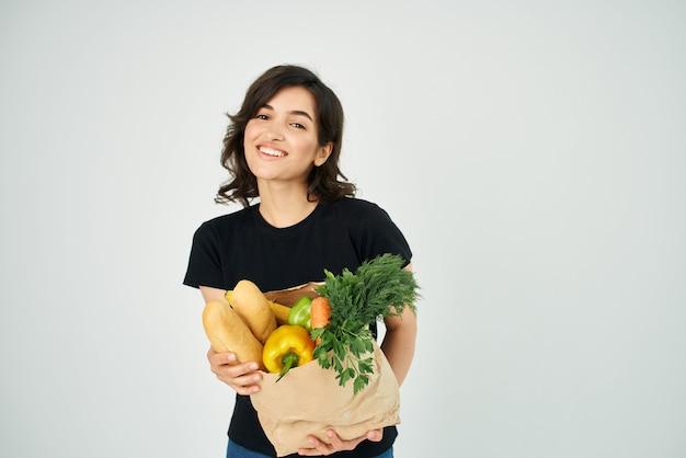 Mulher alegre com um pacote de produtos hortícolas, alimentos saudáveis, luz de fundo