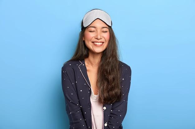 Mulher alegre com um sorriso agradável e cheio de dentes, usa pijama confortável e máscara de dormir, gosta da rotina de dormir