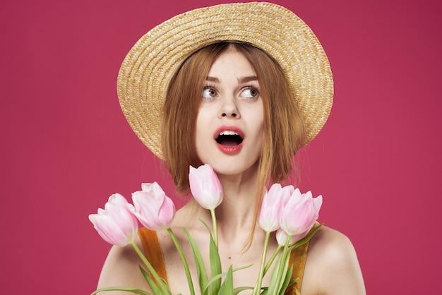 Mulher alegre com um vestido de chapéu e um buquê de flores fundo rosa close-up