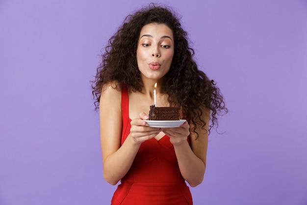 Mulher alegre com um vestido vermelho segurando um pedaço de bolo de aniversário com uma vela, isolado sobre a parede violeta