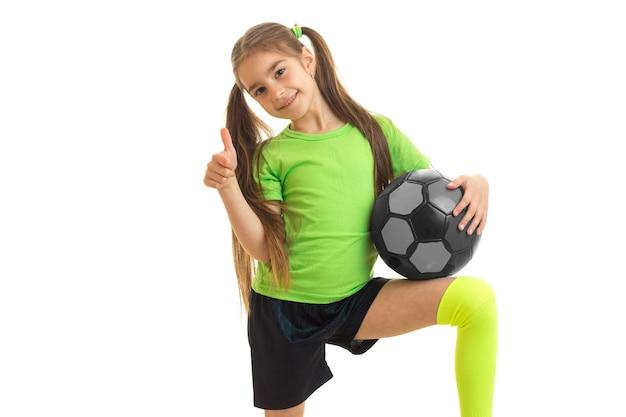 Mulher alegre com uma bola de futebol mostra os polegares para cima e sorrisos isolados no branco
