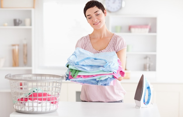 Mulher alegre com uma pilha de roupas